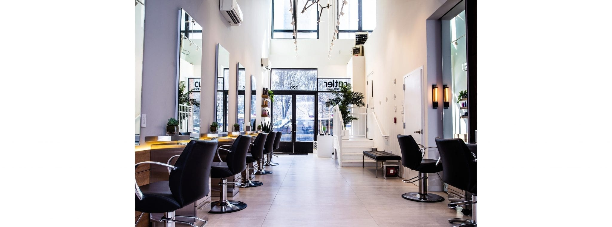 Interior of Cutler Salon in NYC with clean white walls large windows and salon stations neatly lined up on the sides