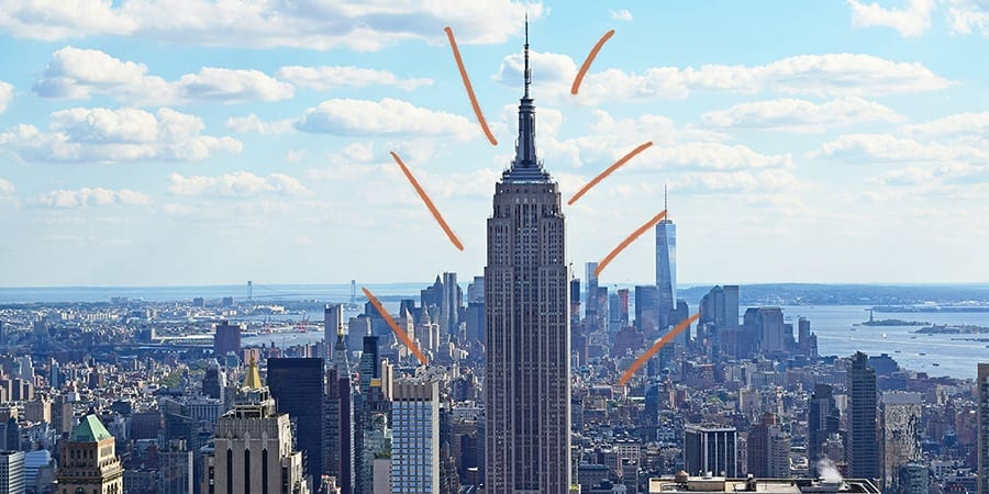 empire state building in the daytime amidst NYC cityscape and orange brush marks as graphical decoration