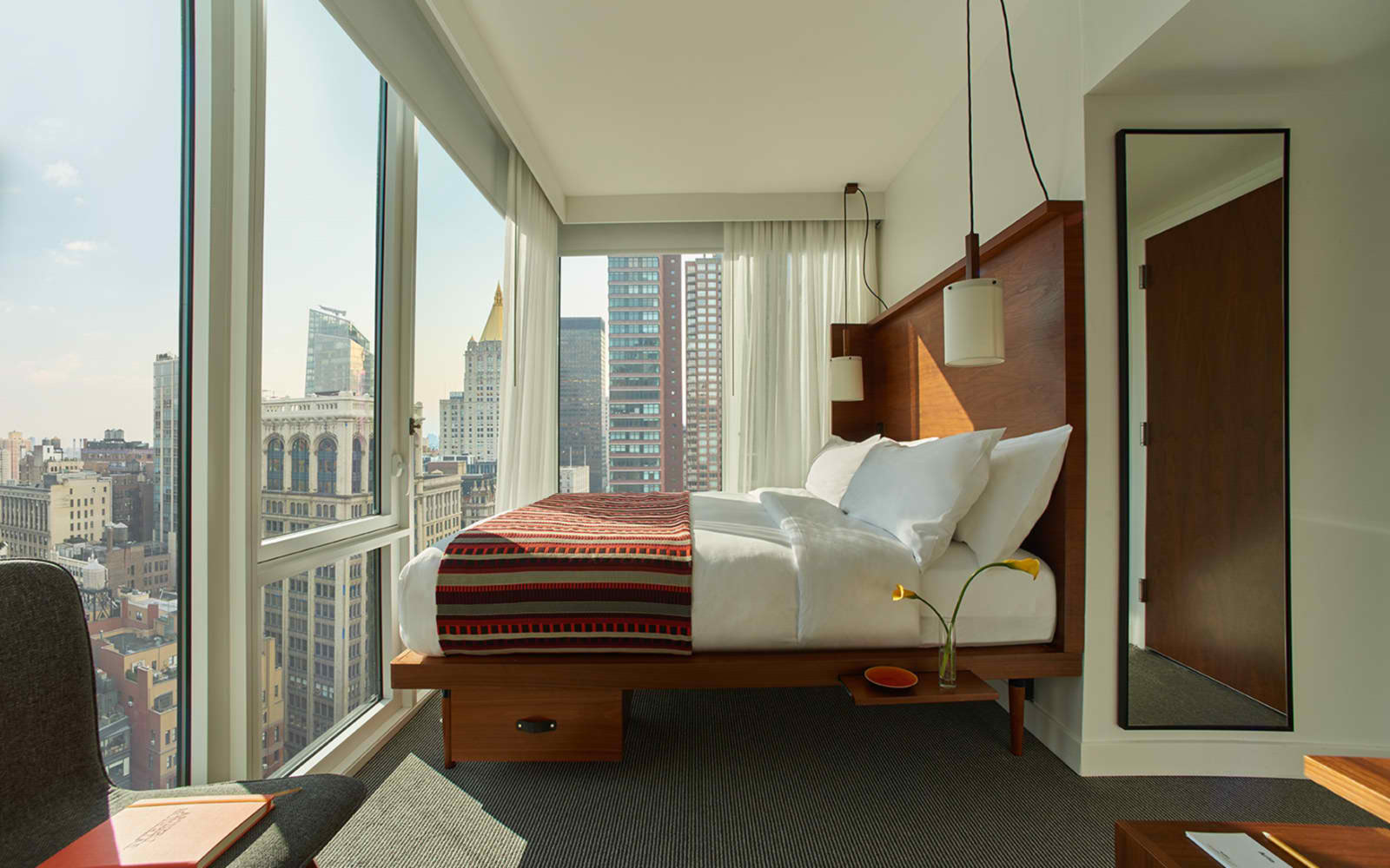 Arlo NoMad King Sky room with a large bed face floor to ceiling windows with city view