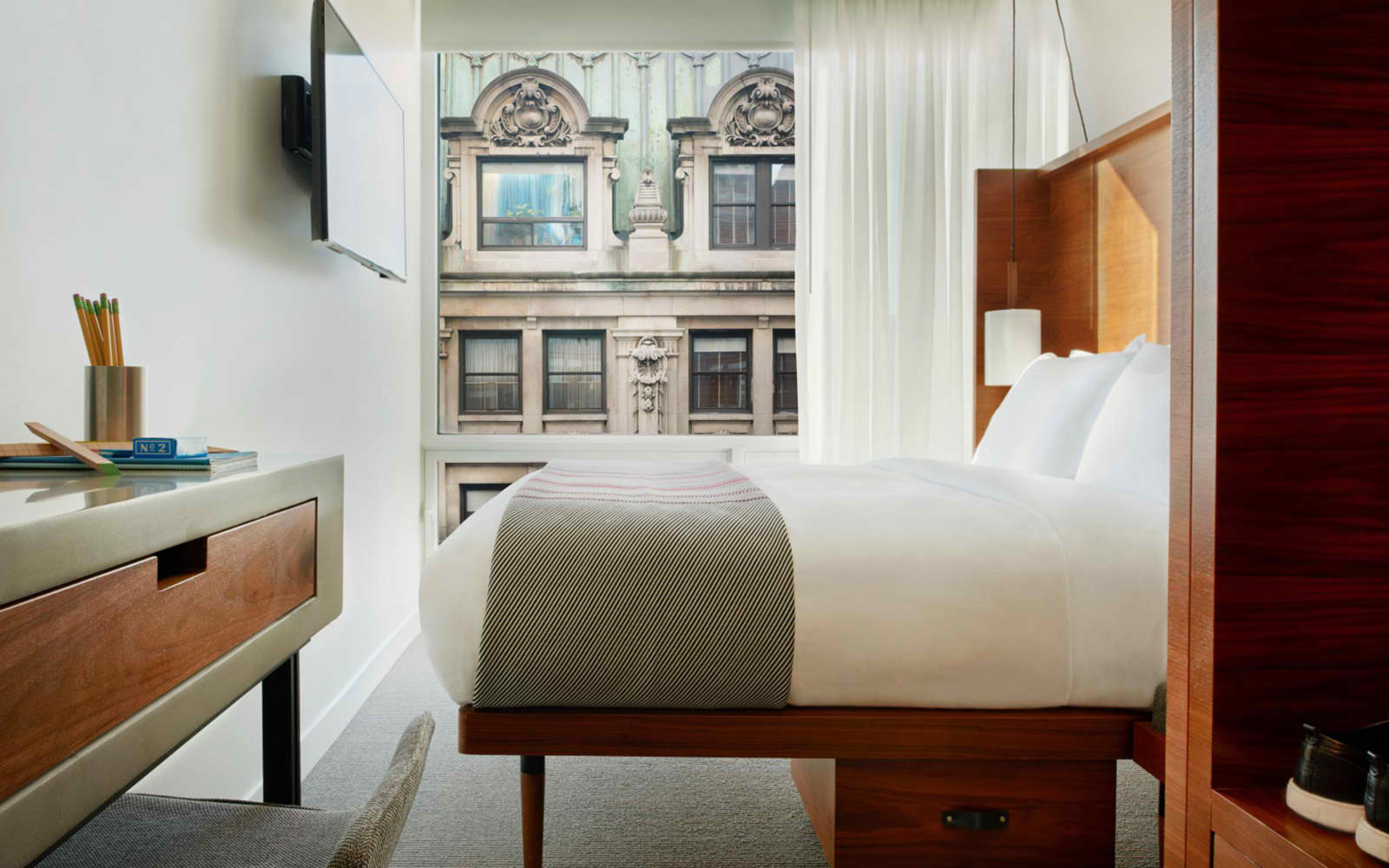 Queen Urban Bed room in NYC NoMad hotel with desk to the left and bed centered in front of wall television and large window overlooking the city