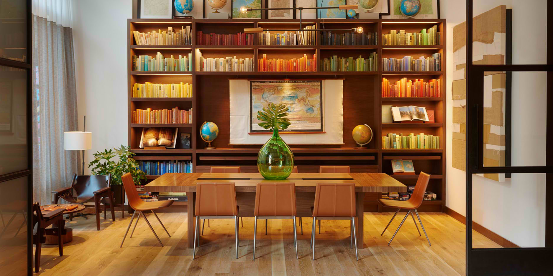 Arlo NoMad Studio with long wooden table centered in room and plan and large shelf in the back filled with colorful books and globes