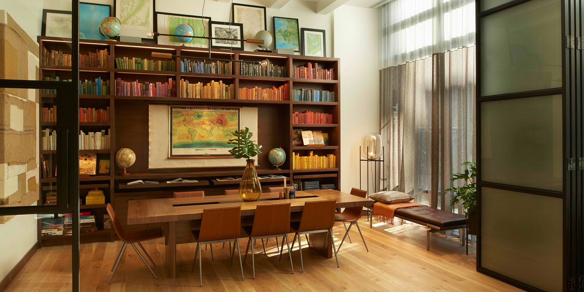 Arlo NoMad studio space with large shelf of colorful books and globes and dramed maps and a long wooden table in the center of the room