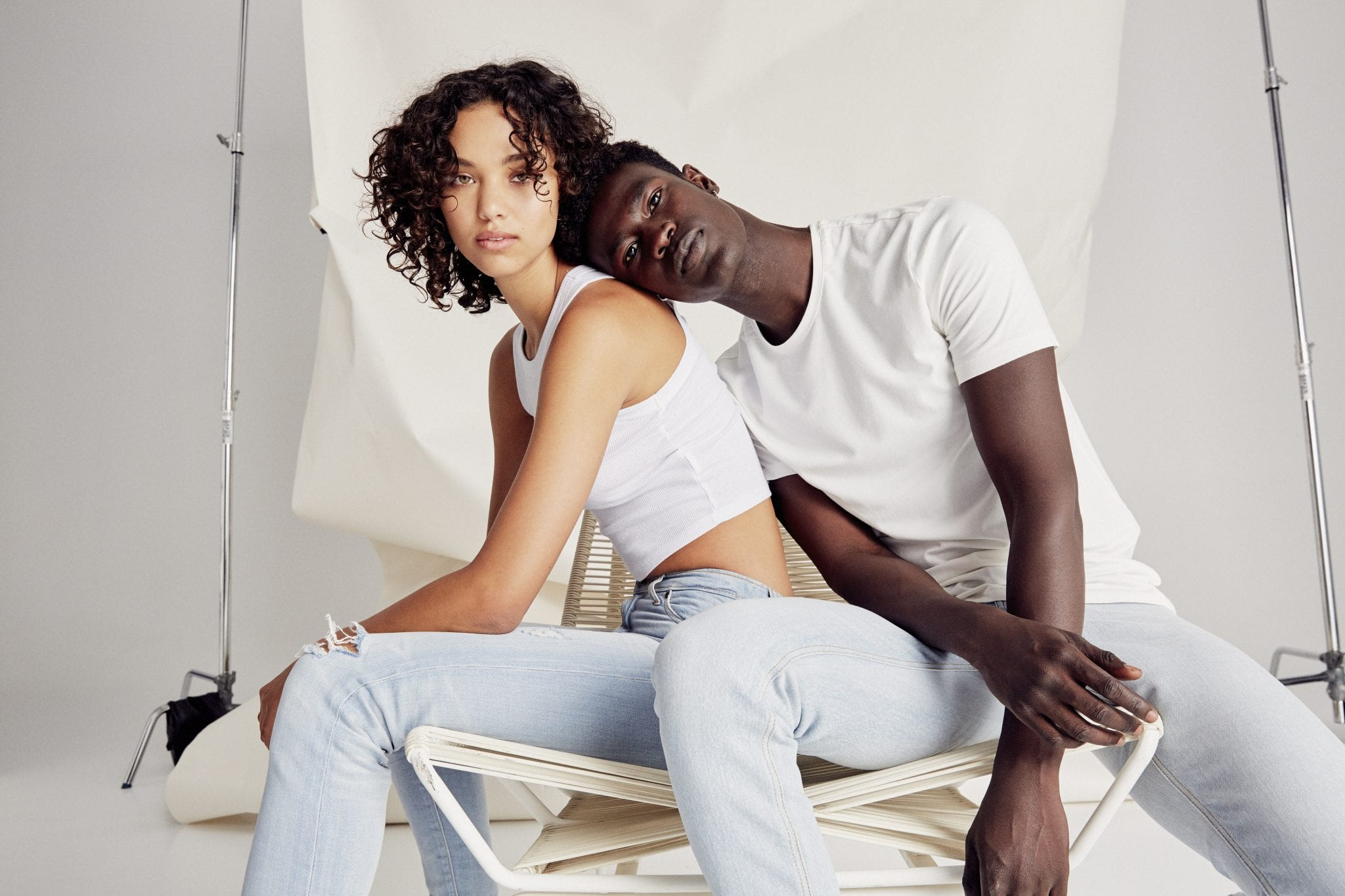 girl and guy in light sustainable jeans sitting in a photoshoot
