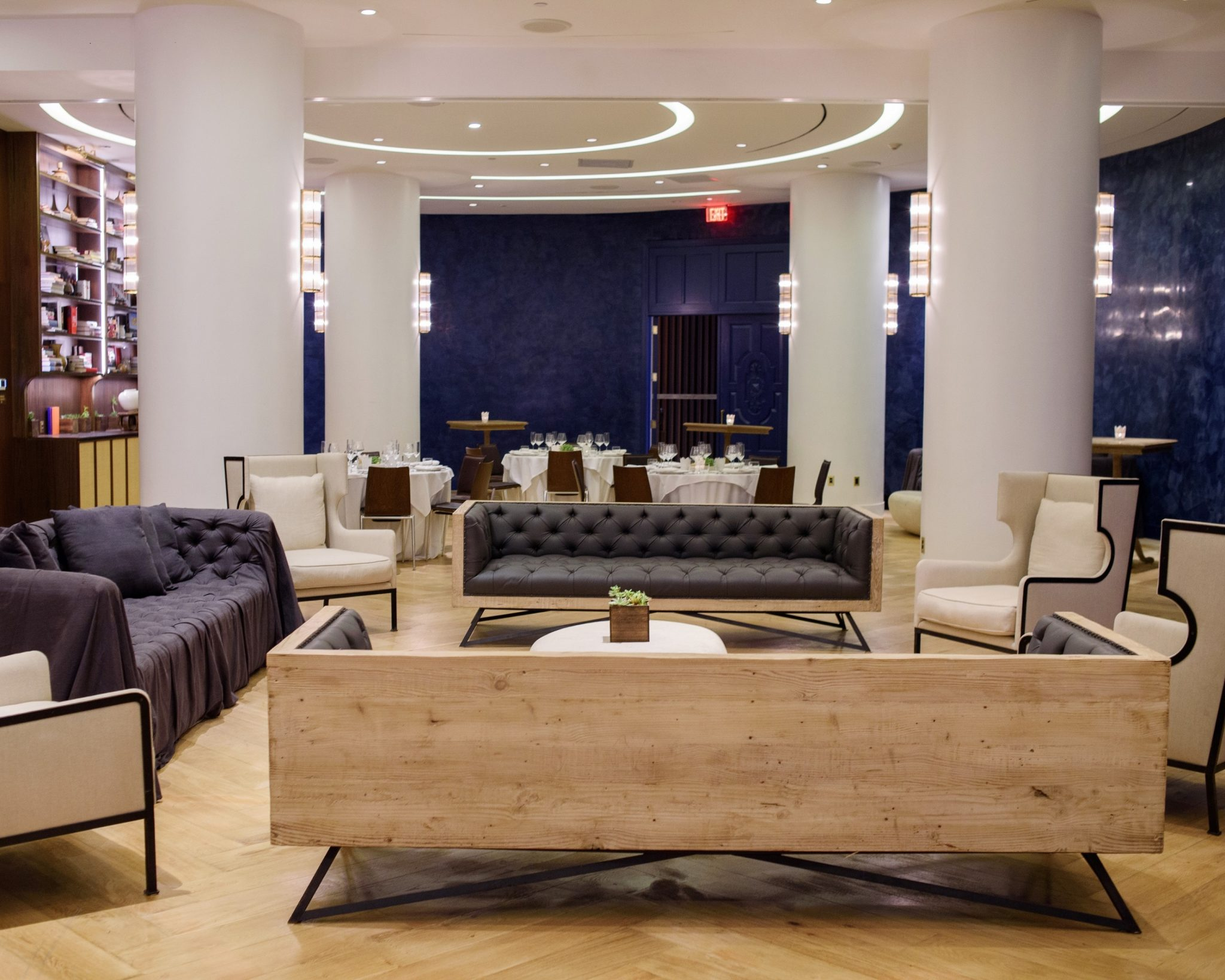 tufted blue gray sofas in middle of room with blue walls bar and four pillars