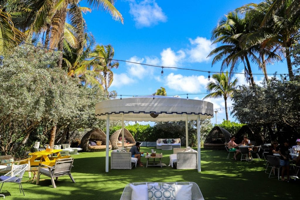 outdoor area with people lounging in white gazebo surrounded by trees