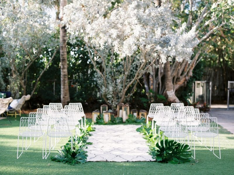 outdoor wedding venue with white walkway and white chairs lined up