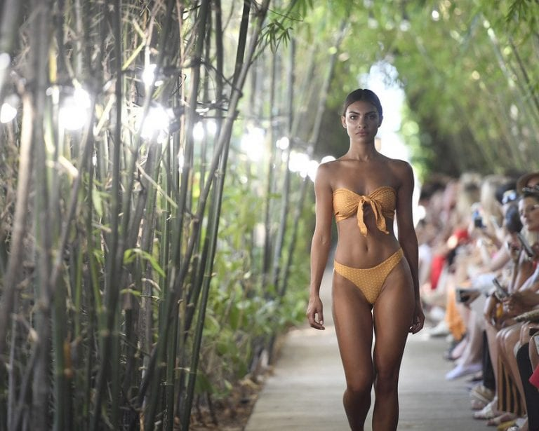 woman in yellow bikini walking in runway show down outdoor green tunnel walkway