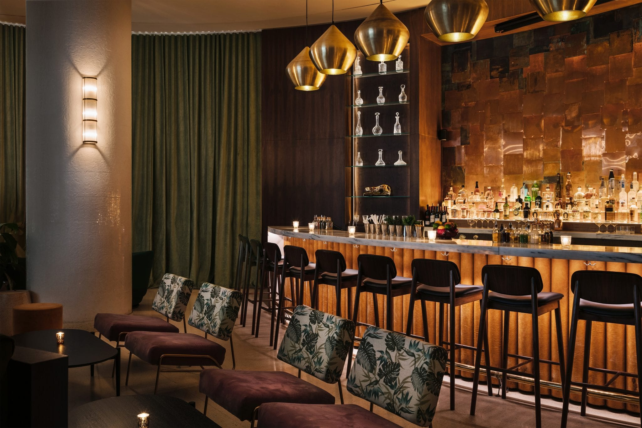 semi circular bar with high chairs and a green curtain and additional seating next to bar with patterned chairs