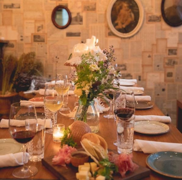 Interior of Arlo NoMad space with decorated table setting with wines and flowers