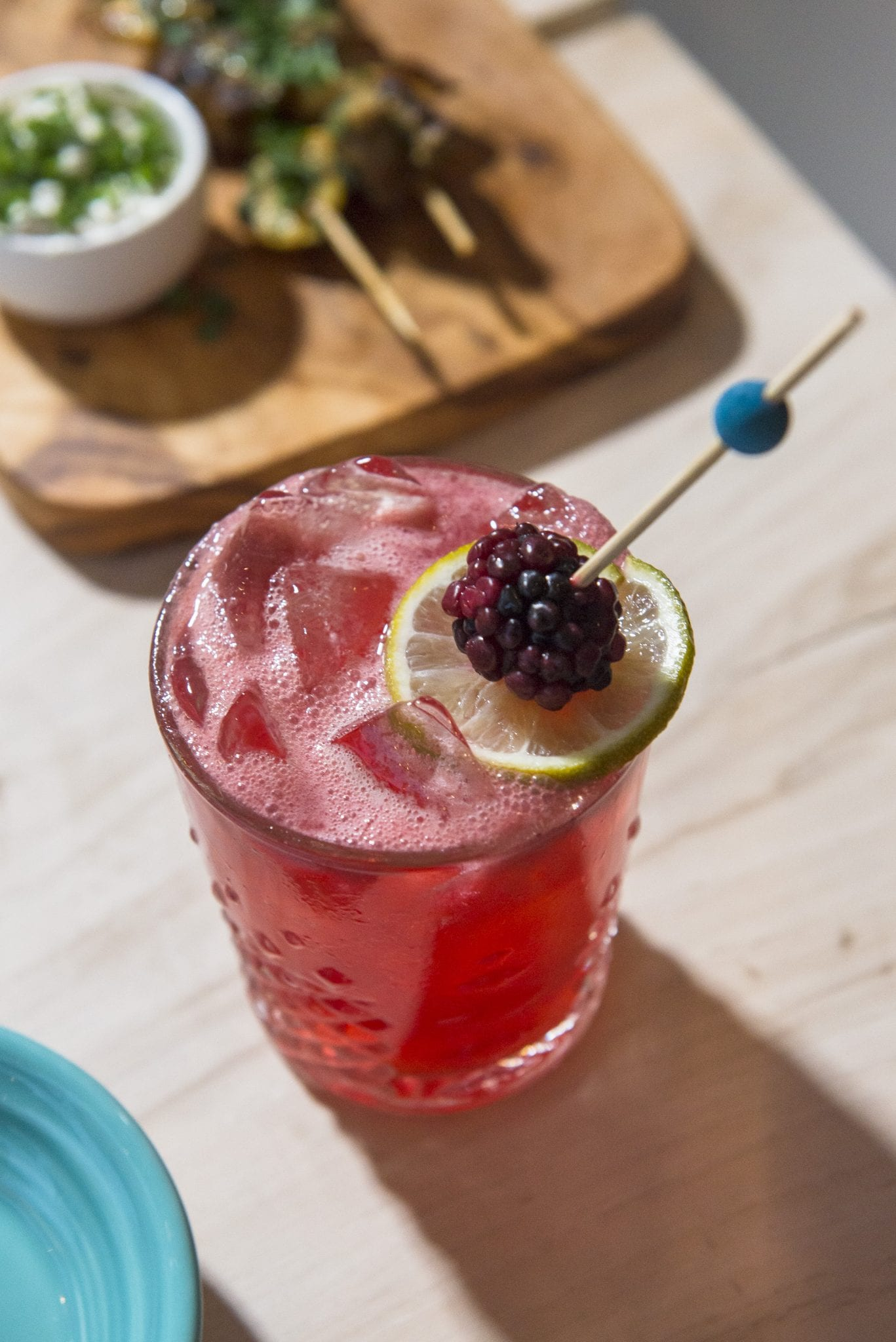 Iced red cocktail with raspberry and lime garnish