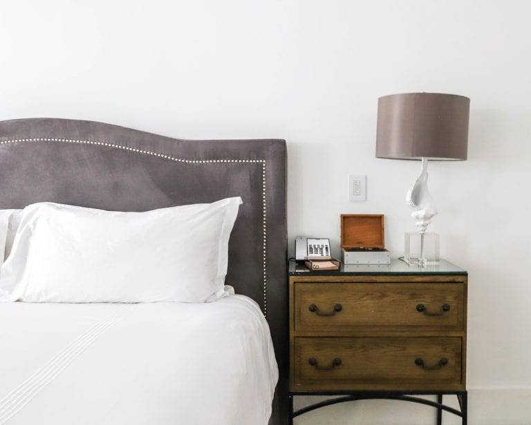 bedside table with lamp and drawers next to accessible king bed
