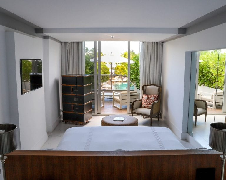Hotel guestroom with balcony terrace and minibar and wall mirror