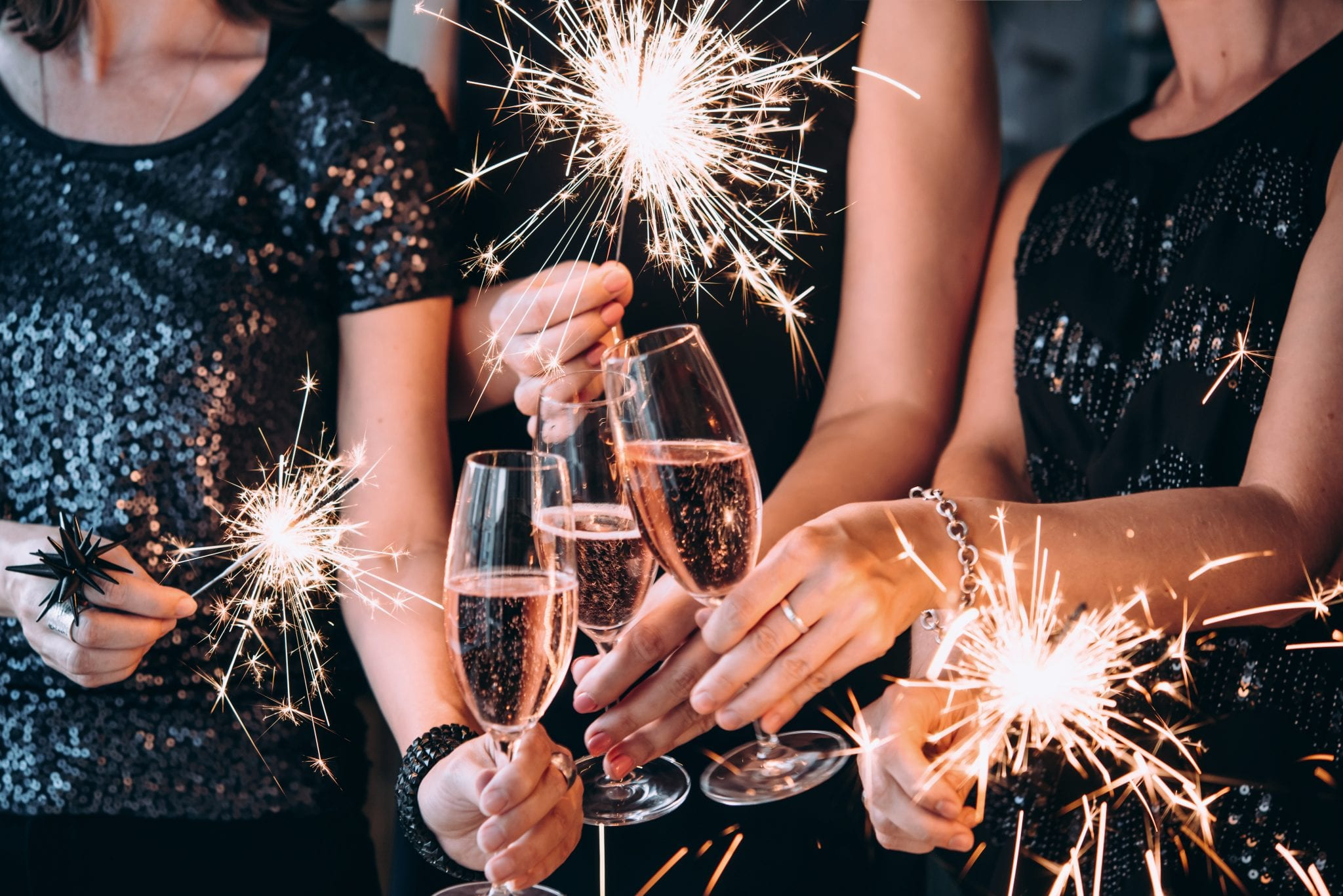 woman holding champagne glasses and sparklers