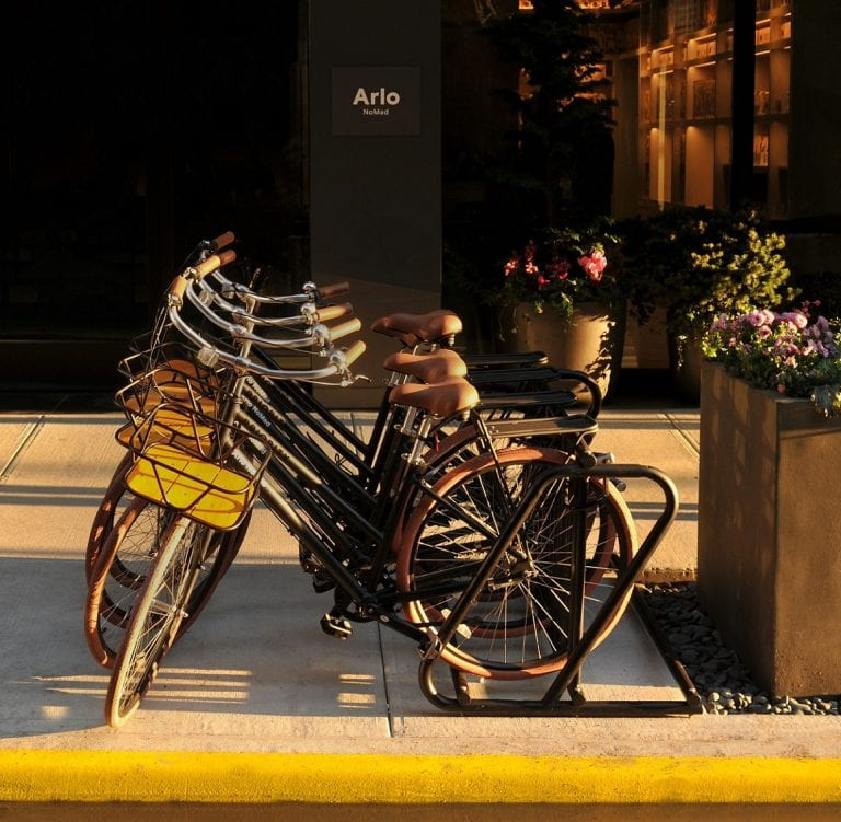 Four Arlo NoMad bikes on bike rack outdoors in front of the hotel