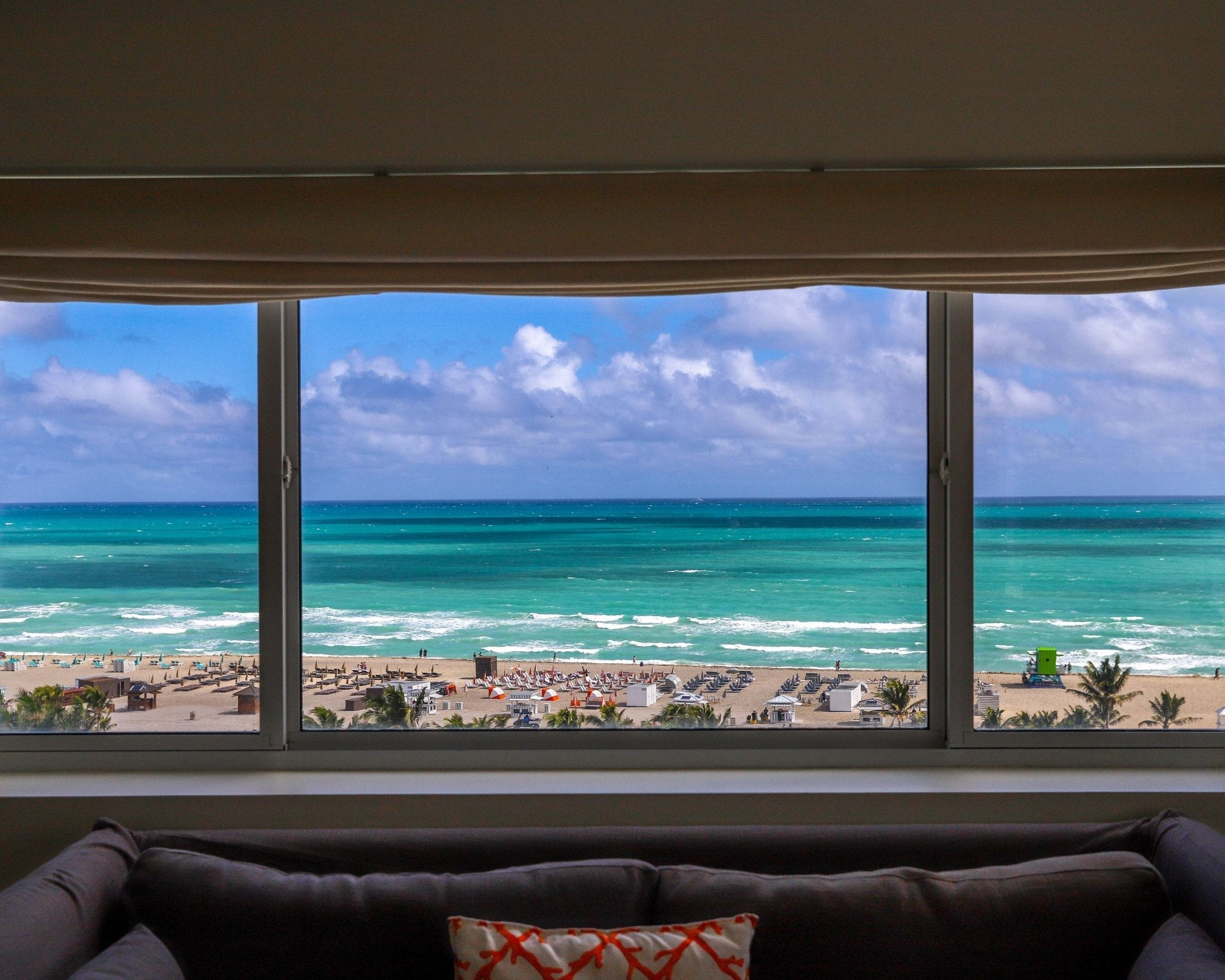 window showing view of blue green ocean and beach