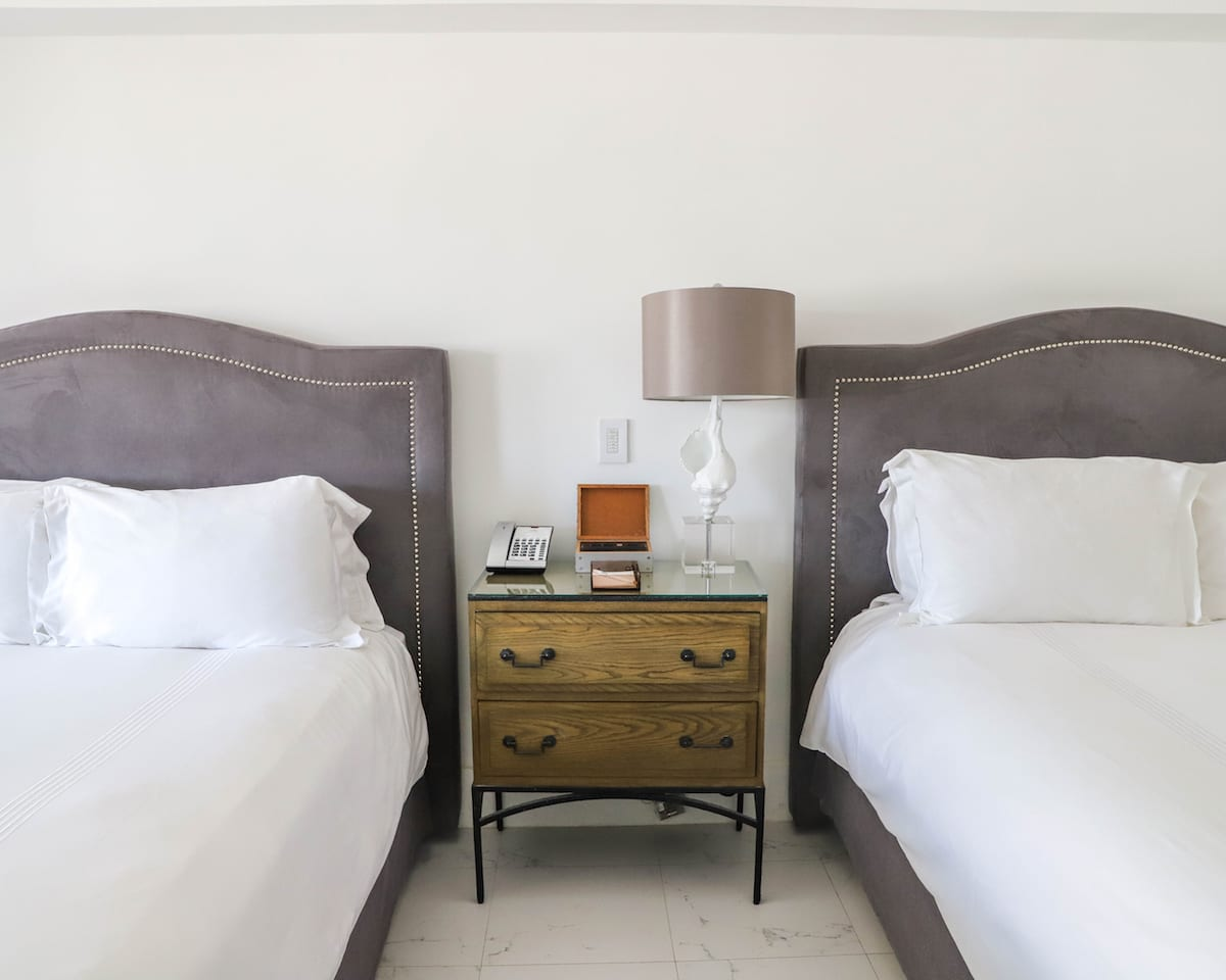 bedside table with lamp, two drawers, and phone in between two queen beds