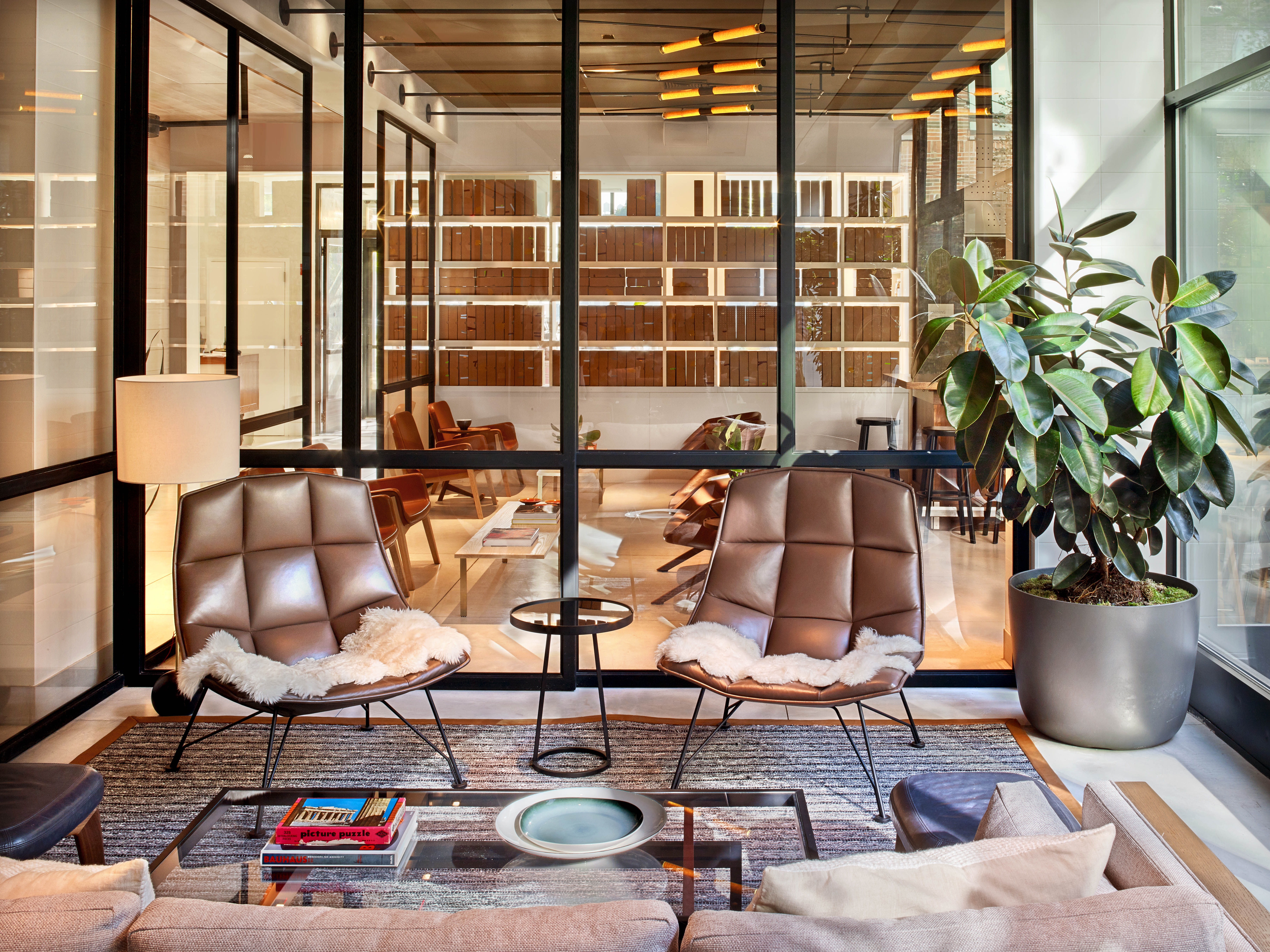 Two brown chairs and large windows in Arlo SoHo living room area