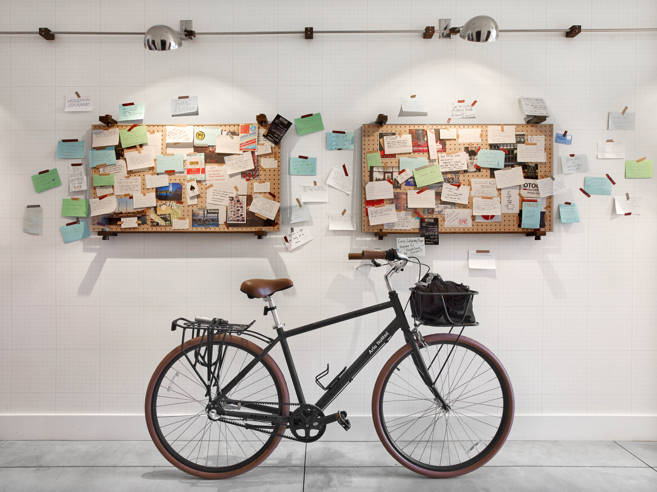 A bike indoors in front of two messenger boards