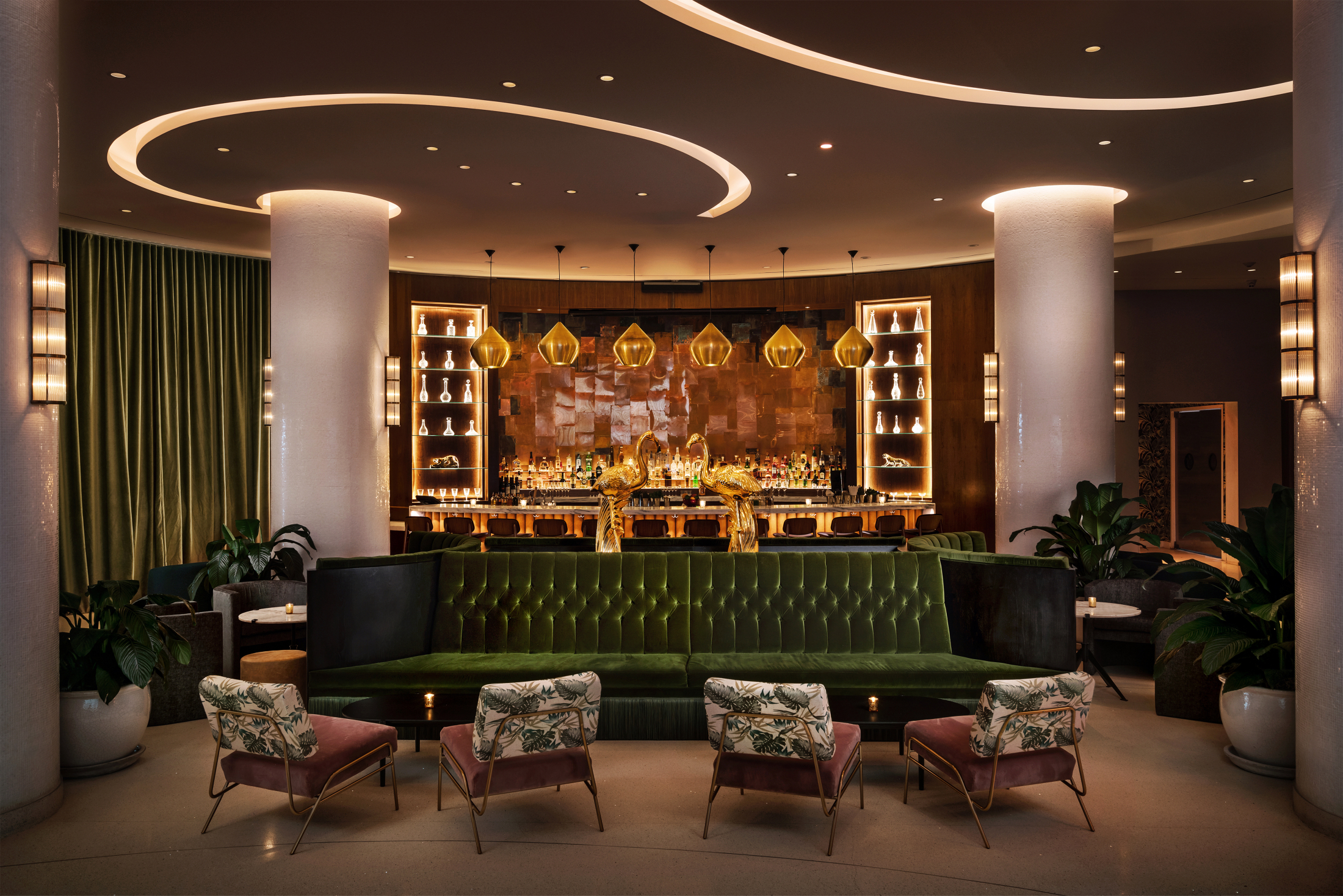 Dim semi circle bar and seating area with large pillars plush green velvet couch and green velvet curtains