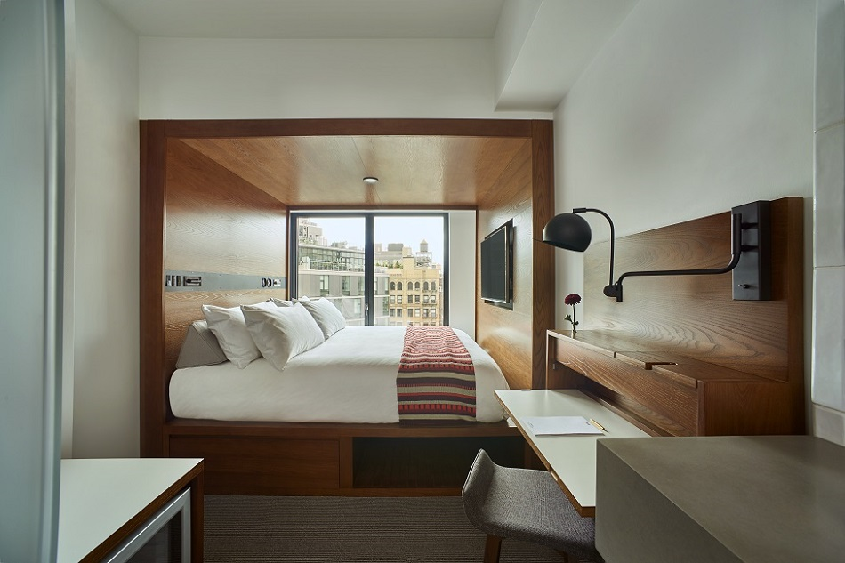 Arlo SoHo guest room with bed in wooden nook and large window