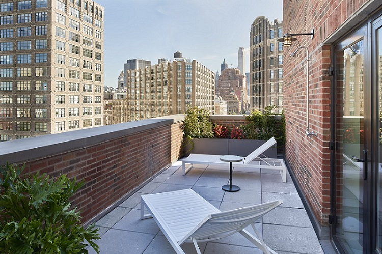 Outdoor terrace area of Arlo SoHo Twin room with views of city and two lounge chairs