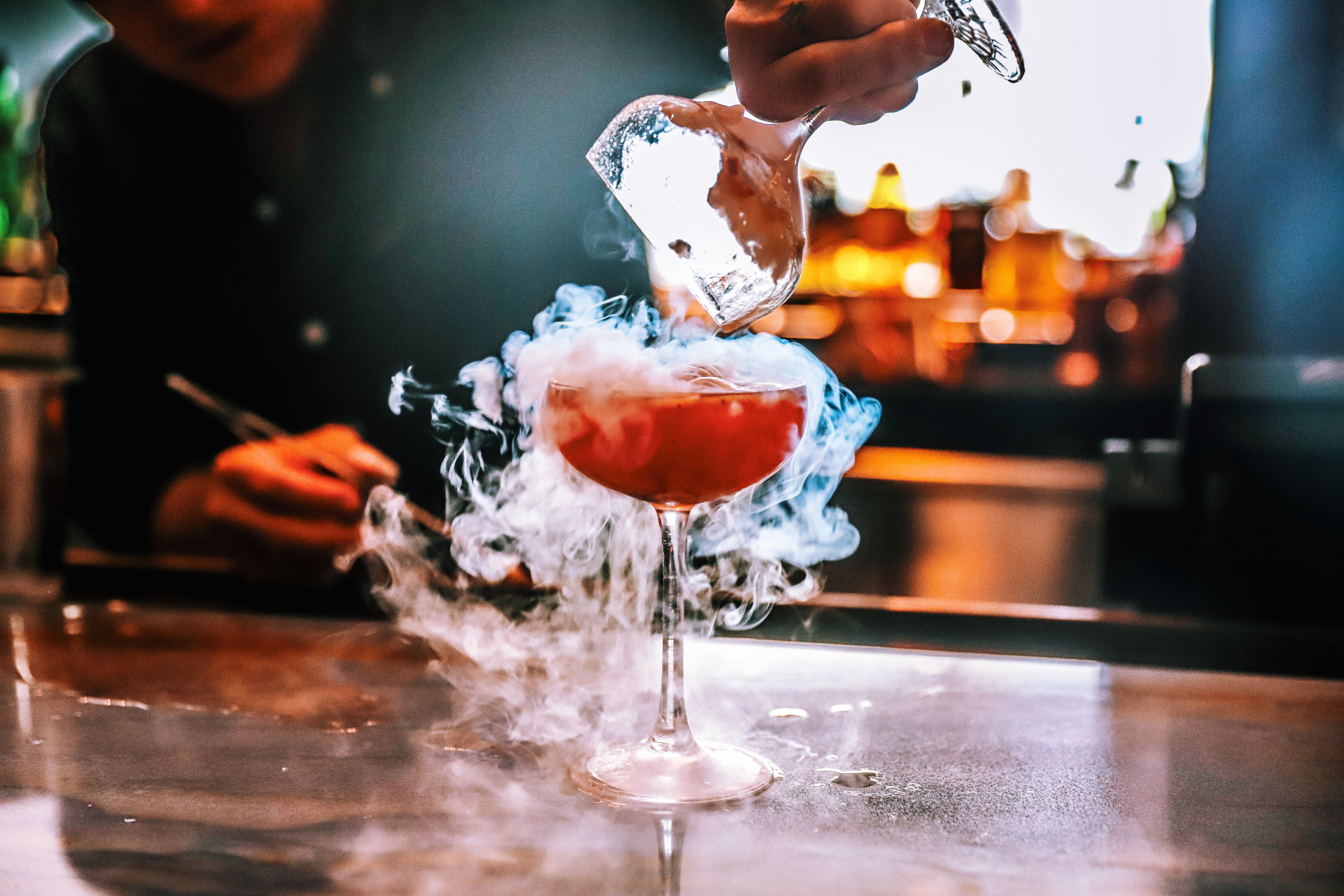 Bartender making a red cocktail with smoking dry ice effect