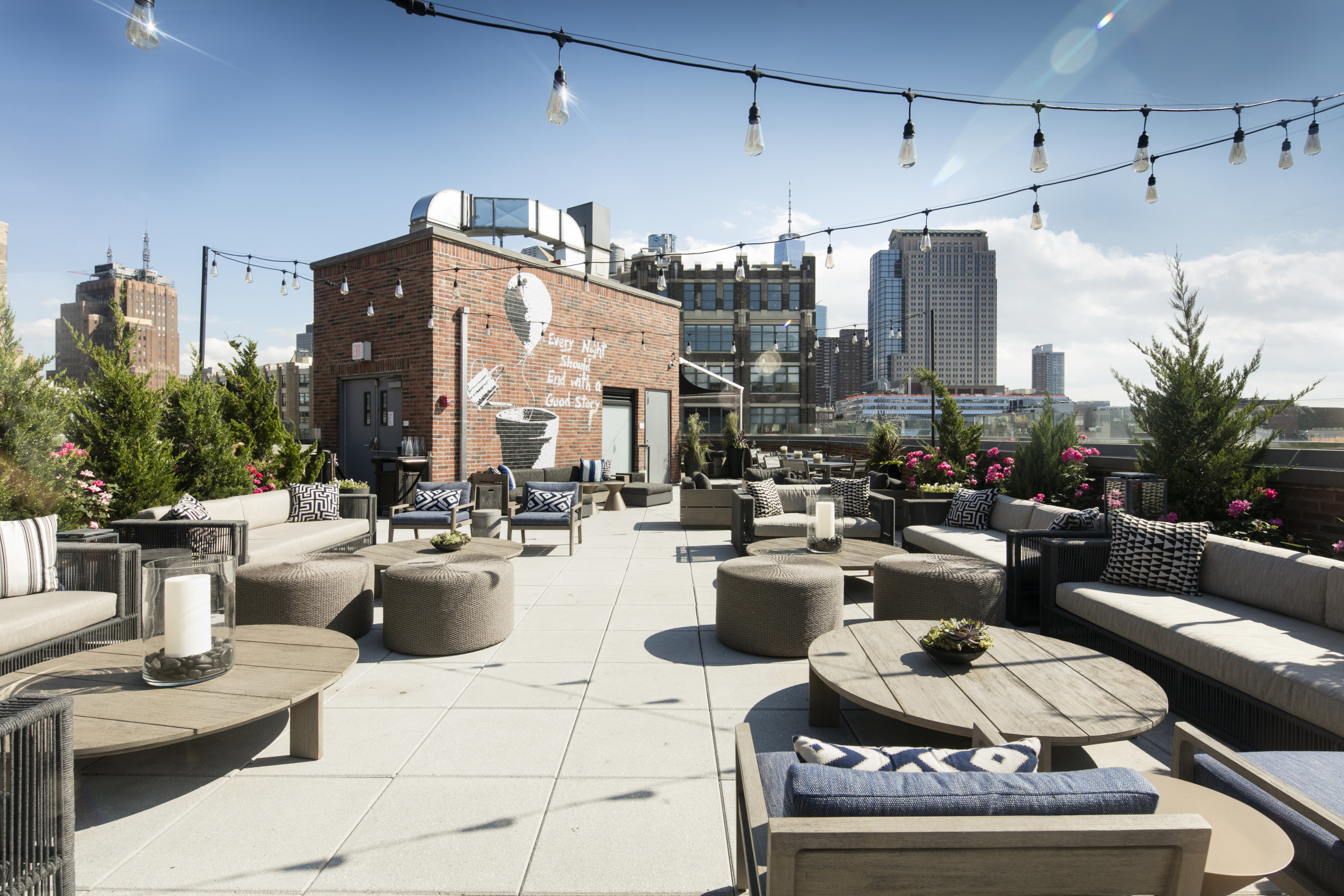 Rooftop space in Arlo SoHo with many seating areas and mural in the back