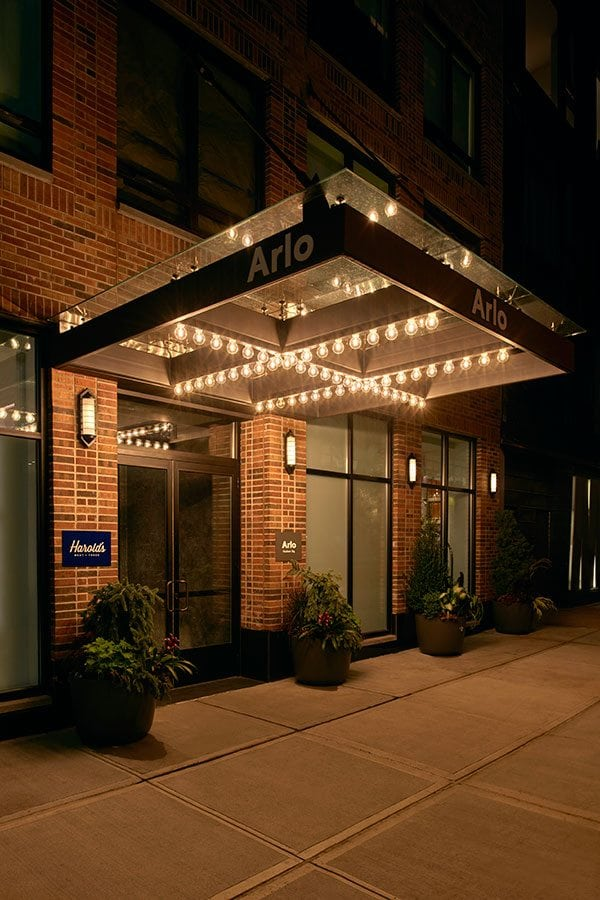 Exterior and entrance of Arlo SoHo at night with lights lit up
