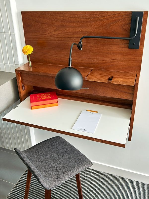 Close up of brown wooden flip down desk and grey chair in Arlo SoHo guest room