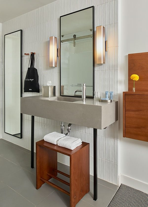 Guest room vanity with sink and rectangular mirrors and different amenities