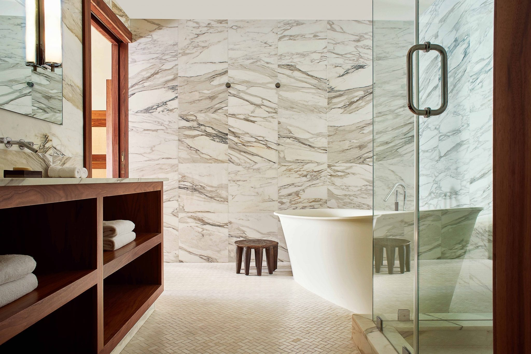 marble walled bathroom with glass encased shower and white standalone bathtub
