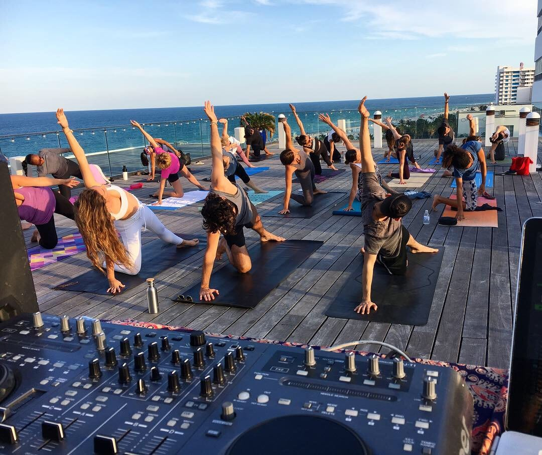 colorful mats and female instructor teaching yoga outdoors on terrace overlooking beach