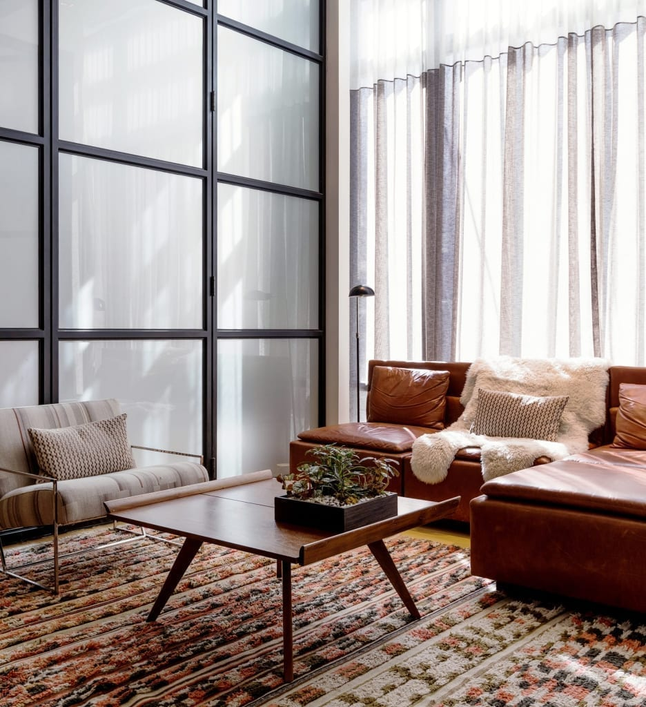 Interior space of Arlo NoMad studio with glass divider to the right and an L shaped leather sofa in the middle along with a flat wooden coffee table and translucent white drapes