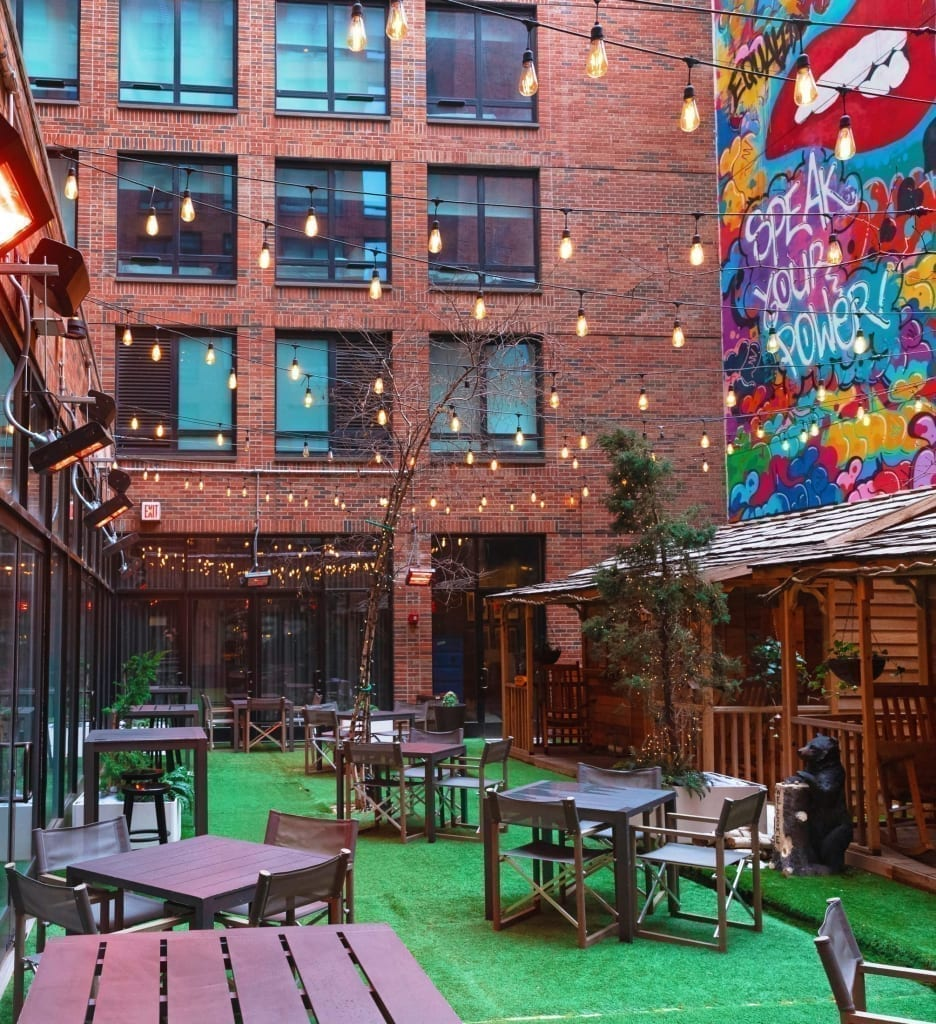 Outdoor Courtyard at Arlo SoHo with rainbow mural to the left and tables on green turf grass and cedar cabins