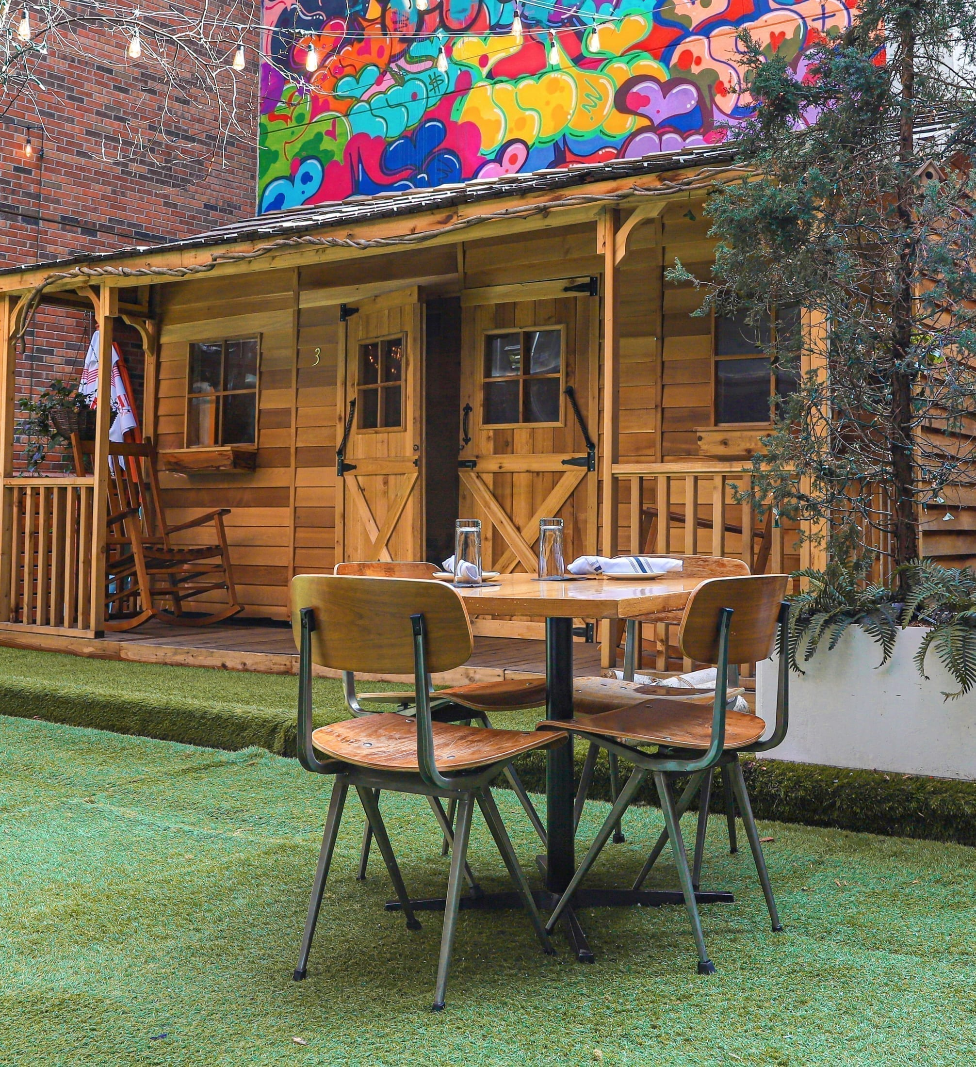 Wooden dining tables on grass outdoors in Arlo SoHo Courtyard with cedar cabin in the background and a multicolored mural wall and string lights