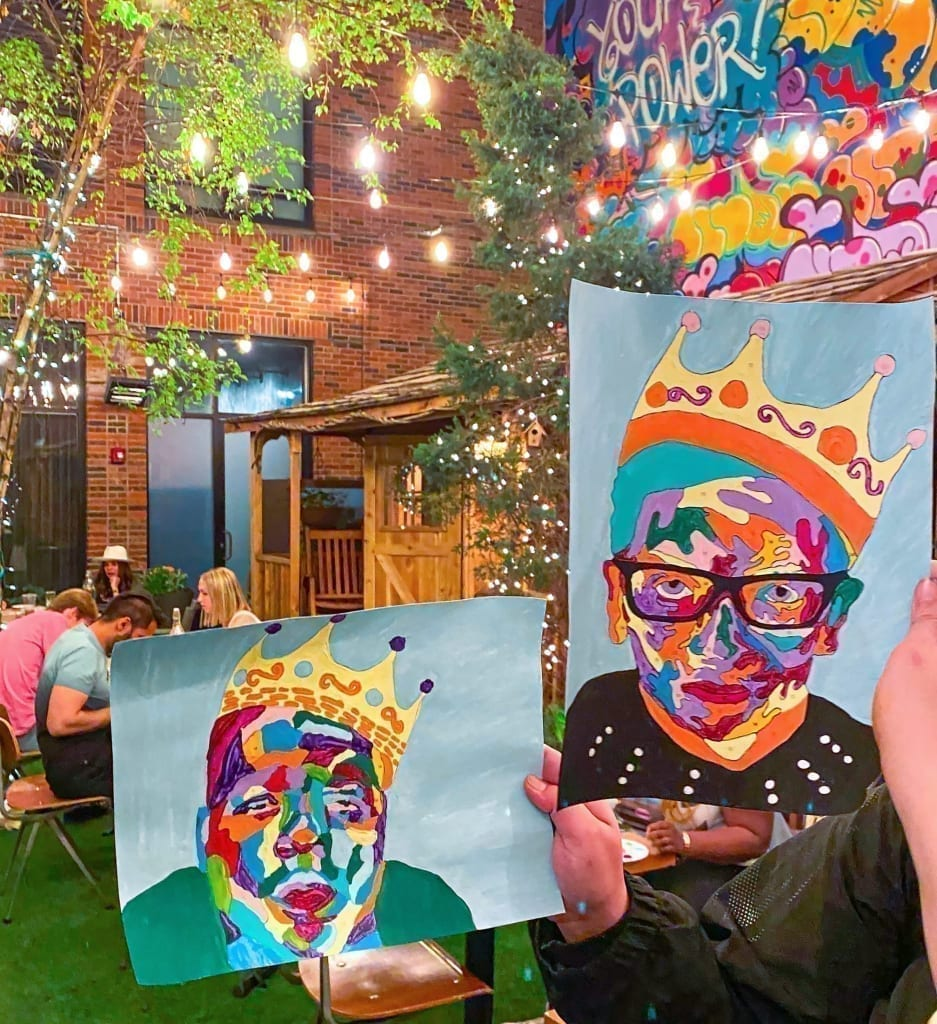 Arlo soho outdoor courtyard event with hand holding up two paintings to the left is biggie smalls and to the right is ruth bader ginsburg. there are string lights hanging above and a cedar cabin and a mural behind.