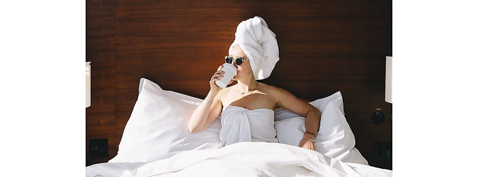 woman sitting on bed in arlo nomad guestroom and wearing sunglasses and a hair towel and drinking a cup of hot coffee and looking towards the sunny window to the left