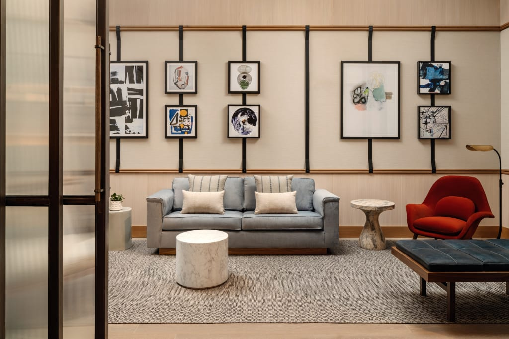 Alcove room with sliding opaque doors from the left and gray sofa in the middle with red love seat and tufted chaise lounge to the right and many paintings on the wall
