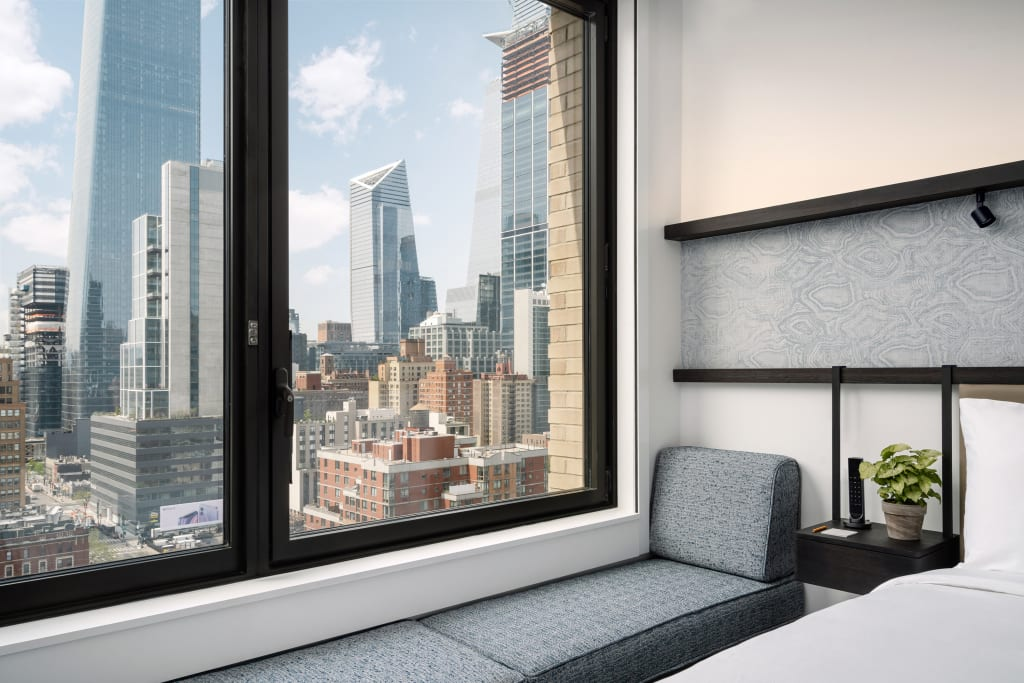 Large window to the left overlooking the city skyline and a gray seating area next to the window