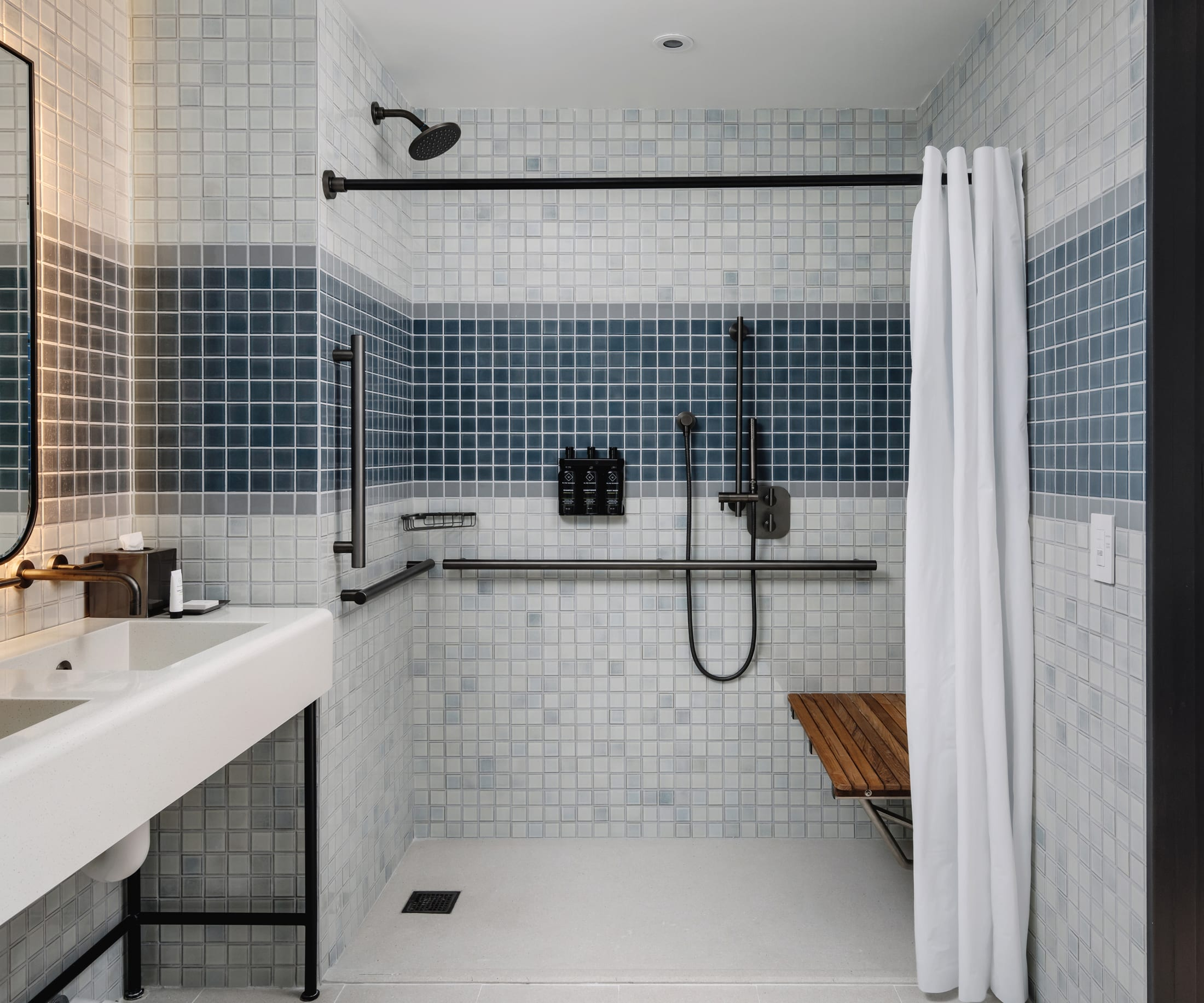 Arlo Midtown guest bathroom with white and blue tiled walls and a rounded edge backlit mirror in the center above a white sink and to the left wall is a globe light and to the right is the glass shower door with towel hanging