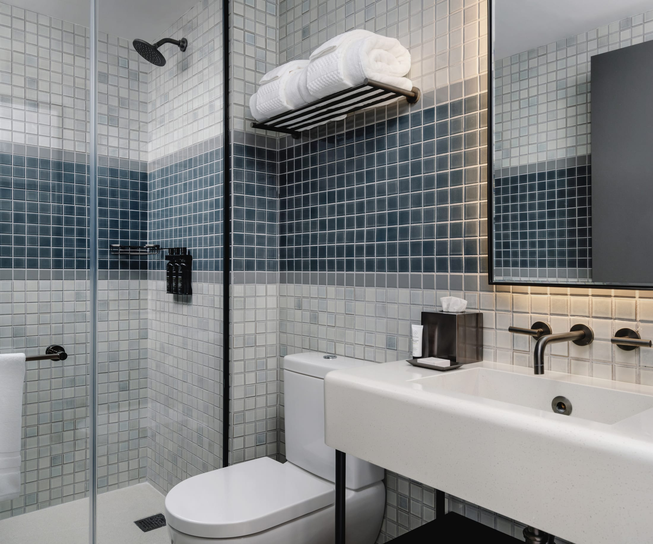 blue and gray tiled bathroom walls with glass shower on the left and backlit mirror above white sink on the right