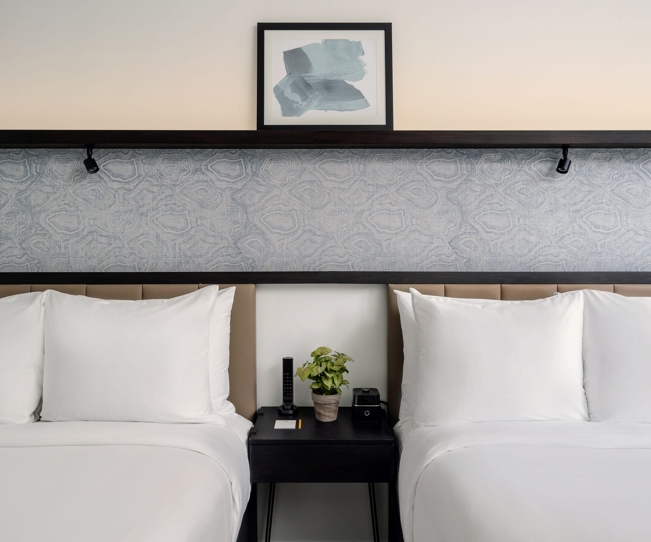 Two beds side by side in Midtown guestroom with painting in the center and a night stand in the center
