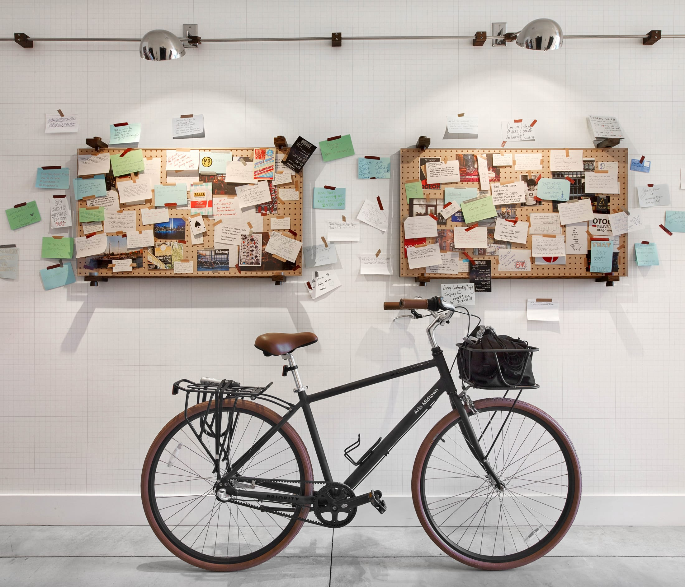Arlo Midtown bike in front of sharing wall full of notes and cards