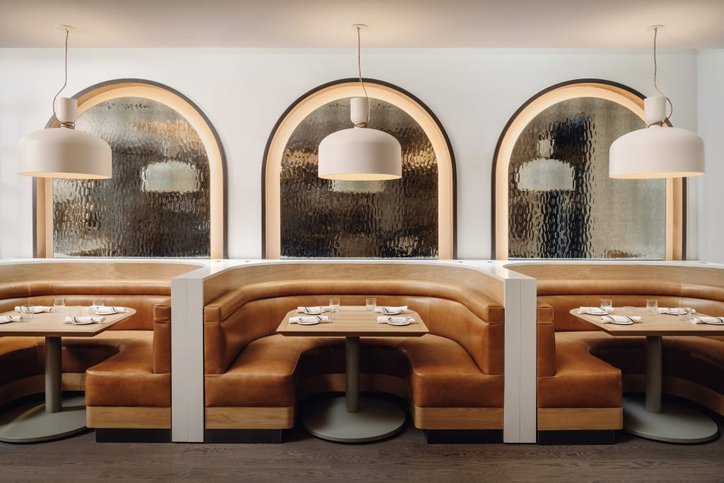 Arlo Midtown restaurant interior with three semi circle booths with tanned leather seats and arched mirrors in the back