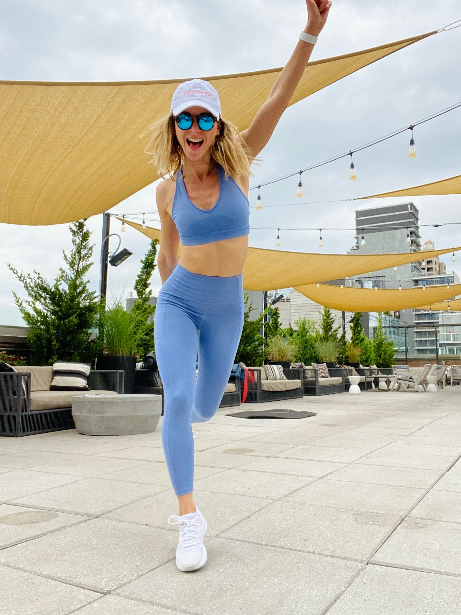 Woman on Arlo SoHo rooftop in blue workout outfit under yellow fabric awning dancing and working out