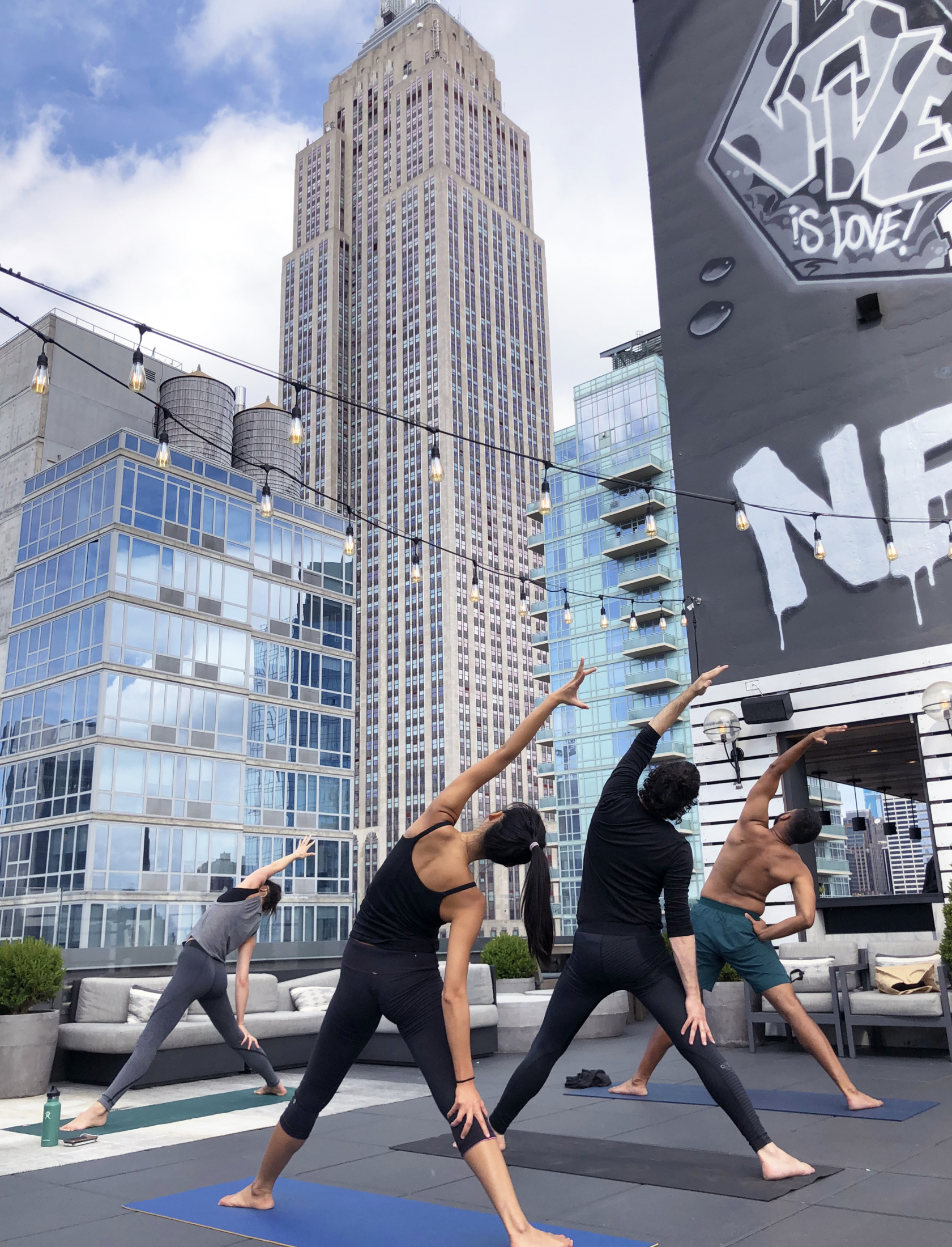 Outdoor rooftop yoga at Arlo NoMad with people standing and stretching on yoga mats in front of the empire state building