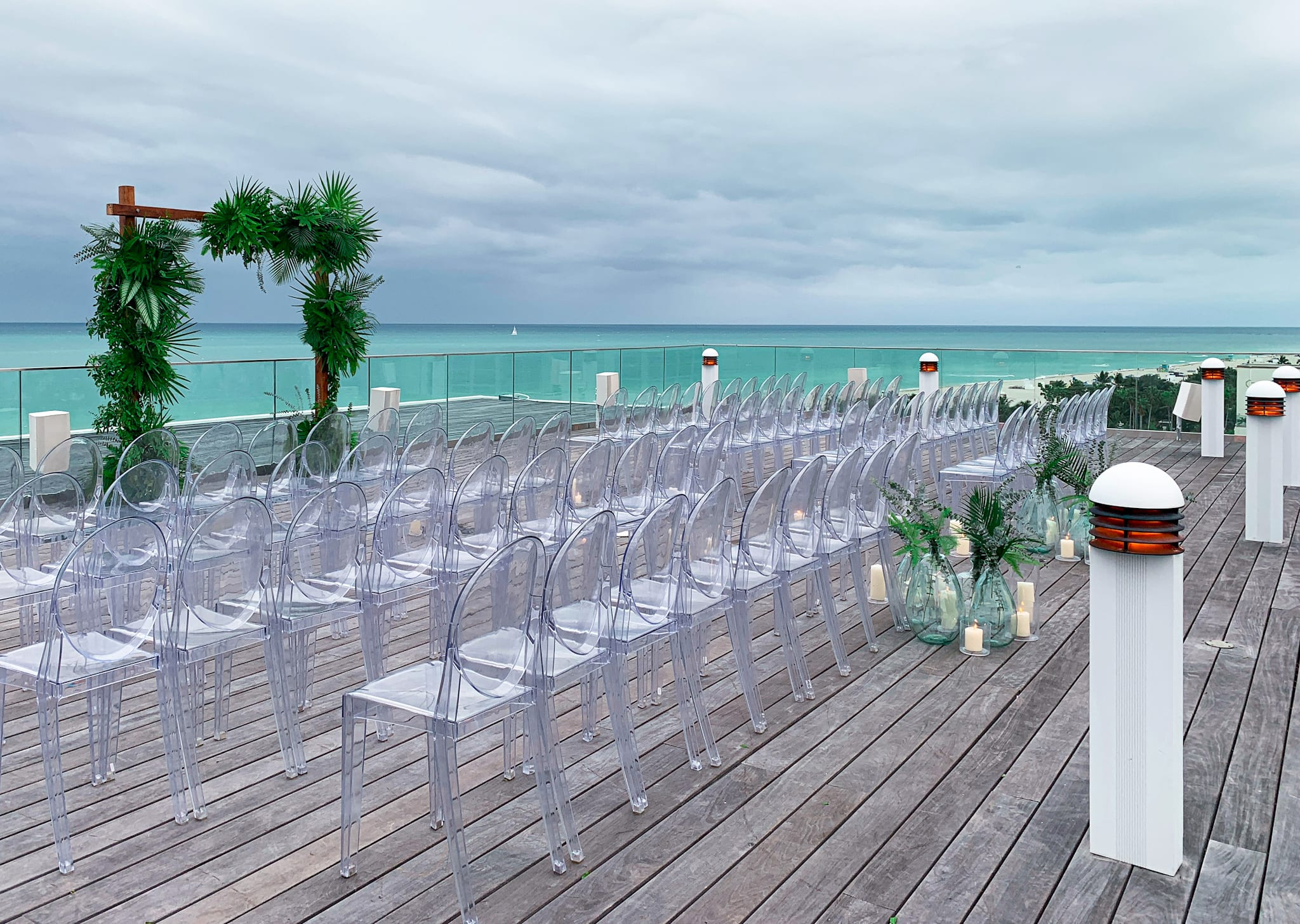 Rows of clear chairs set up on wooden ocean terrace3 floor with green arch in the front