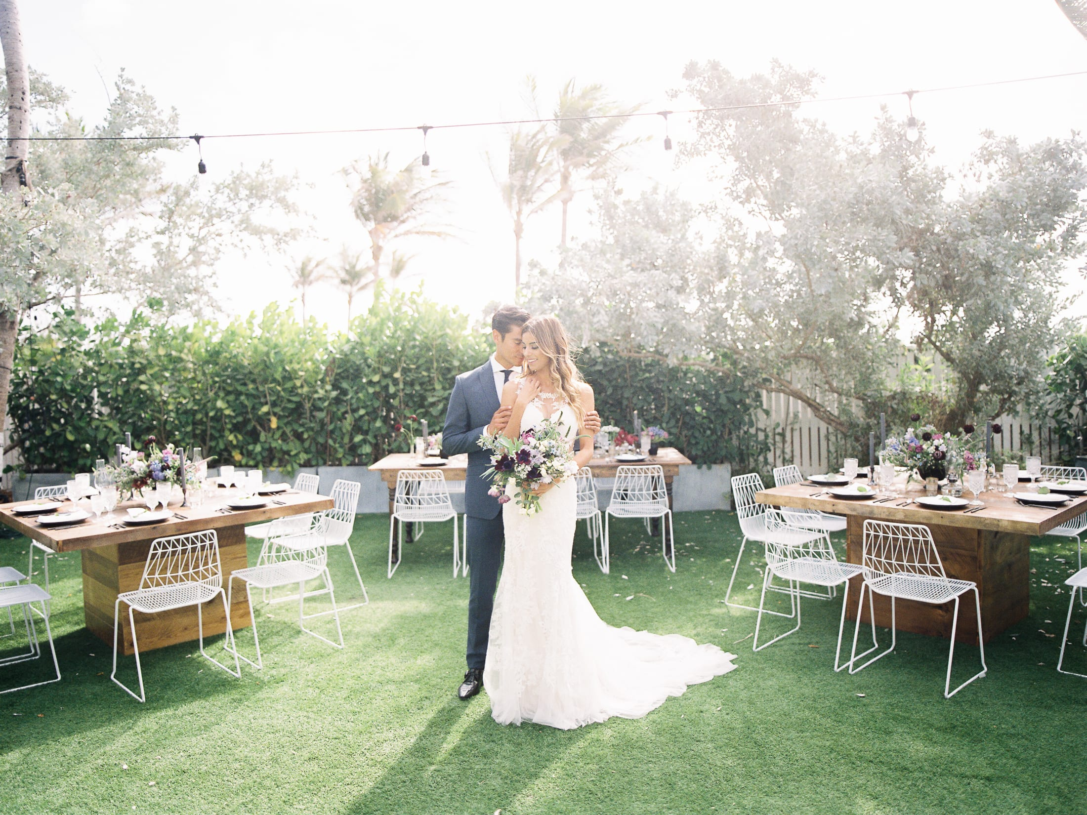 Nautilus by Arlo backyard with green turf and plants and bride and groom embracing in the middle surrounded by wooden tables