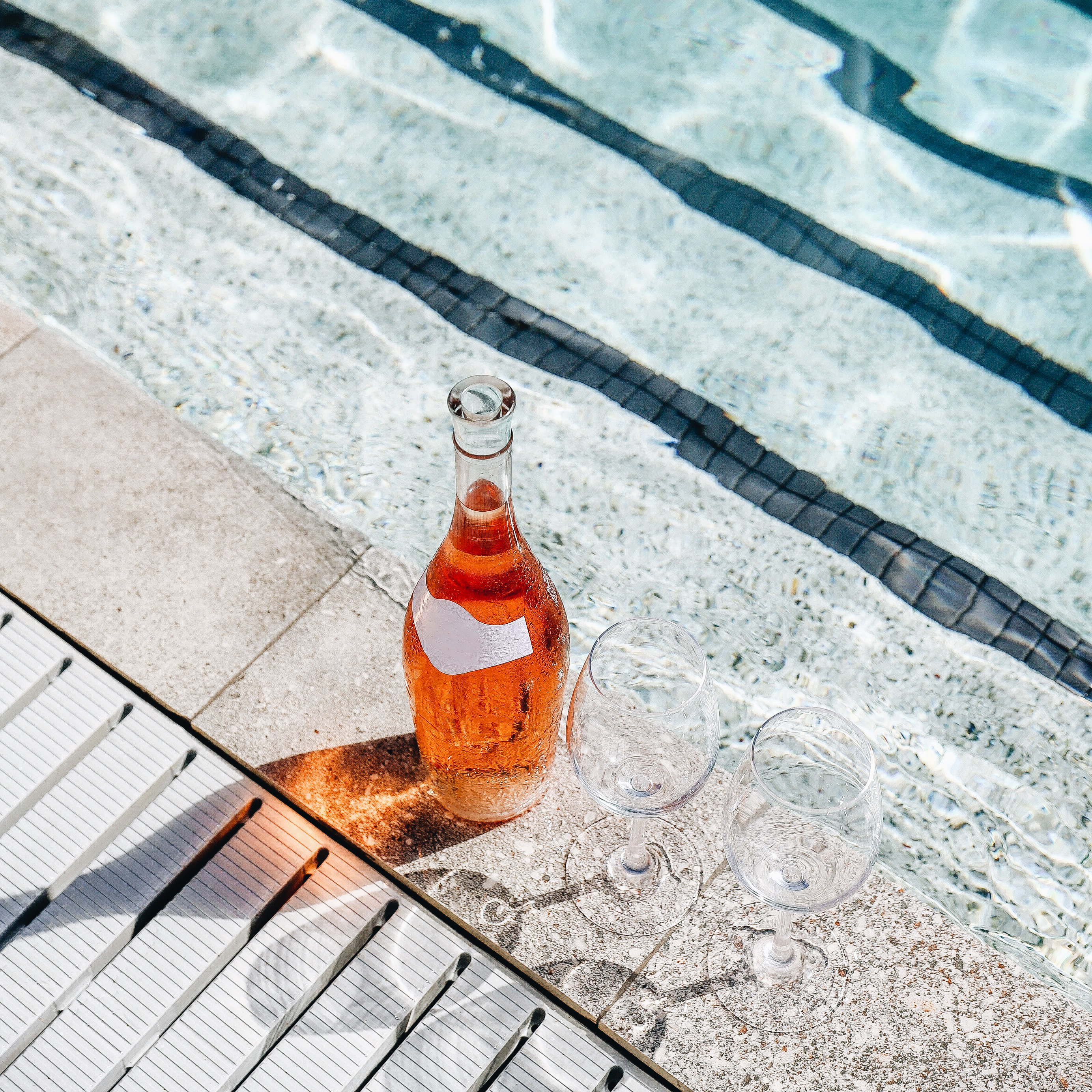 Nautilus by Arlo hotel pool with bottle of rose on pool deck and two glasses
