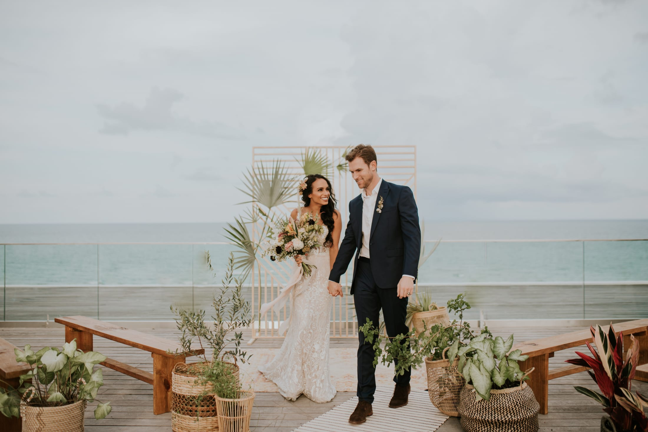 Bride and groom on Nautilus hotel ocean front terrace holding hands